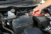 Car mechanic uses battery jumper cables to charge dead battery — Stock Photo