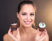 Portrait of beautiful young girl with chocolate cupcake on brown background — Stock Photo