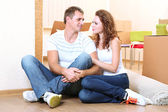 Young couple with boxes in new home on room background — Foto de Stock