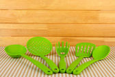Plastic kitchen utensils on tablecloth on wooden background — Stock Photo