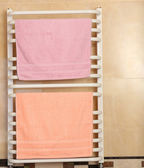 Color towels on radiator in bathroom — Stock Photo