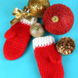 Red winter mittens with Christmas toys on blue wooden table — Foto de Stock