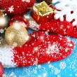 Red winter mittens with Christmas toys on blue wooden table — Foto Stock