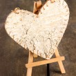 Decorative heart on easel, on wooden background — Lizenzfreies Foto