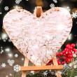 Decorative heart on easel, on wooden table, on shiny background — Стоковая фотография