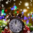 Christmas decorations and retro alarm clock on wooden table, on bright background — Stock Photo