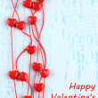 Heart-shaped beads on string on wooden background — Foto Stock