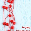 Heart-shaped beads on string on wooden background — 图库照片