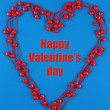 Heart-shaped beads on string on fabric background — Stock Photo