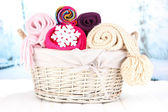 Warm knitted scarves in basket on winter background — Stock Photo