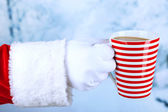 Santa holding mug in his hand, on light background — Stock Photo