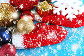 Red winter mittens with Christmas toys on blue wooden table — Stock Photo