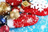 Mitaines d'hiver rouge avec des jouets de Noël sur une table en bois bleue — Photo