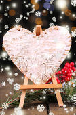 Decorative heart on easel, on wooden table, on shiny background — Foto Stock
