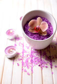 Still life with beautiful blooming orchid flower, towel and bowl with sea salt, on color wooden background — 图库照片