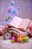 Composition with plaids, candles and Christmas decorations, on white carpet on bright background — Foto de Stock