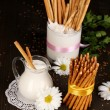 Tasty crispy sticks with pitcher and glass with sour cream on wooden table close-up — Stock Photo