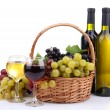 Bottles and glasses of wine and grapes in basket, isolated on white — Stock Photo