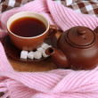 Cup and teapot with scarf on fabric background — Stock Photo