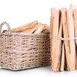 Stock Photo: Stack of firewood in wicker basket isolated on white