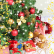 Decorated Christmas tree with gifts on grey wall background — Stock Photo #36867933