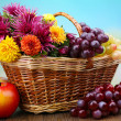 Composition with beautiful flowers in wicker basket and fruits, on bright background — Stock Photo #36869287