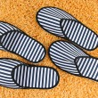 Striped slippers on carpet background — Stok fotoğraf