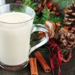 Cup of eggnog with fir branches and Christmas decorations on wooden background — Stock Photo