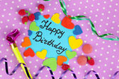 """Card """"Happy Birthday"""" surrounded by festive elements on purple background — Stock Photo"""