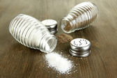 Salt and pepper mills, on wooden background — Stock Photo