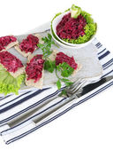 Beet salad on toasts and in plates on board on napkin isolated on white — Stock Photo