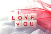 Candles with printed sign I LOVE YOU, on white fabric background — Stock Photo