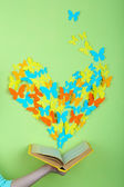 Paper butterflies fly out of book on green wall background — Stock Photo