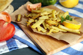 Ruddy fried potatoes on wooden board on table close-up — 图库照片