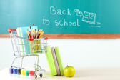 School supplies in supermarket cart on blackboard background — Stock Photo