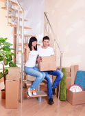 Young couple with boxes in new home on staircase background — Stock fotografie