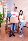 Young couple with boxes in new home on staircase background — Stock Photo