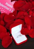 Ring daaromheen rozenblaadjes op houten tafel close-up — Stockfoto