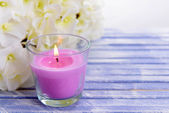 Beautiful colorful candles and flower,on color wooden background — Stock Photo