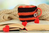 Cup with knitted thing on it and open book close up — Stock Photo
