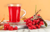 Red berries of viburnum and cup of tea on table on beige background — ストック写真