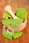 Ginkgo biloba foglie nel mortaio e pillole su fondo in legno — Foto Stock