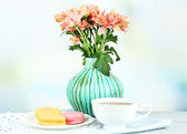 Beautiful flowers in vase, on wooden table, on light background — Stock Photo