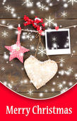 Decorative heart, star and empty photo paper on rope, on wooden background — Stockfoto