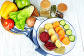 Beautiful sliced vegetables, on plate, on wooden background — 图库照片