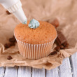 Stock Photo: Confectioner decorating tasty cupcake with butter cream, on color wooden background