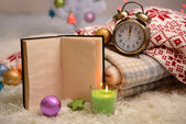Composition with plaids, candles and Christmas decorations, on white carpet on bright background — Stok fotoğraf