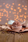 Tasty cupcakes with butter cream, on wooden table, on lights background — Stock Photo