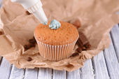 Confectioner decorating tasty cupcake with butter cream, on color wooden background — ストック写真