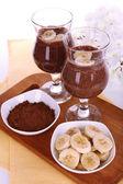 鸡尾酒,香蕉和巧克力在白色背景上的桌子上 — 图库照片